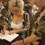 Roberta autographing a book for a resident of ours.