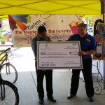 Ronn giving the check to the foster agency.