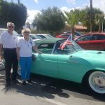 Visitors in front of blue T-Bird.
